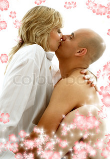 sweet couple playing and kissing in bedroom with flowers