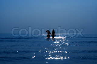 silhouette of two girls holding hands in the sea
