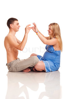 Pregnant woman with her husband kissing by hands Studio shoot on white