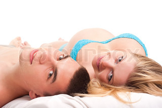 Pregnant woman with her husband laying on white and smiling Studio shoot on white