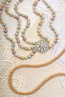Rope and necklace on lace background closeup