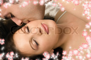 picture of couple cuddling in bed with flowers