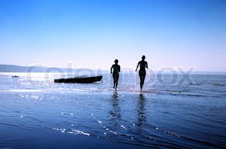 silhouette image of two running girls in water