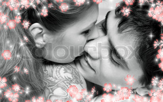 monochrome picture of sweet couple cuddling in bed with flowers