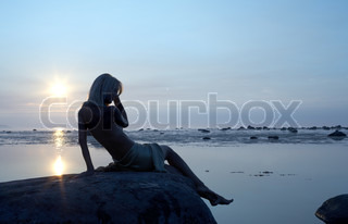 silhouette image of topless lady on the rock