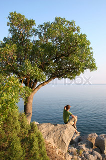Man sitting on the rock under the tree and looking into horizon