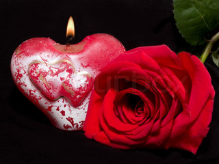valentine's still-life with candle in shape of heart and red rose on the black background focus on the candle