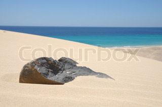 Volcanic black stone in sand of dune on Canary Island Fuerteventura, Spain
