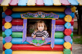 Playful child looking out kid house on playground