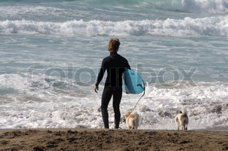 Surfer with his dogs on the beach