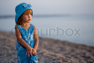 Baby girl in blue dress and hat staying at beach alone and looking into sea