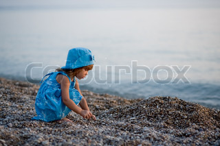 Baby girl in blue dress and hat playing on beach at sunset alone