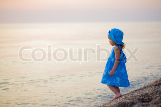 Baby girl in blue dress and hat staying at beach alone and looking into sunset