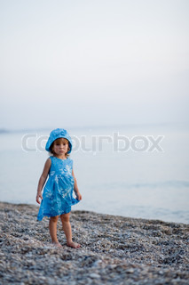 Baby girl in blue dress and hat staying at beach alone