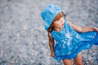 Baby girl in blue dress and hat staying on pebble at beach