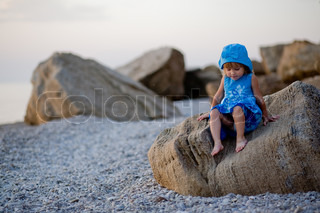 Baby girl in blue dress and hat sitting on stones at sunset beach