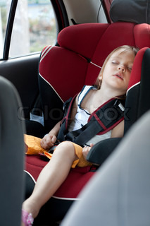 Sleeping child in auto baby seat in car