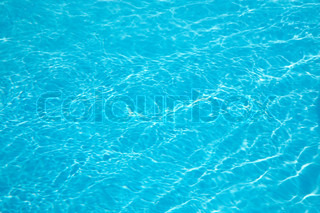 patterns of sunlight rippling o n a swimming pool water surface