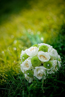 Wedding bouquet with white roses in fresh green grass