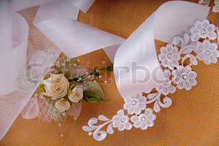 White satin wedding details on beige background and artificial roses