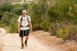 A young male walking on a mountain trail during a hiking trip