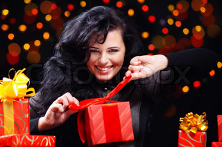 Cute woman with presents at night holiday celebration