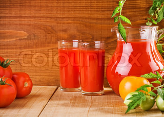 tomato juice in kitchen glassware and tomatoes