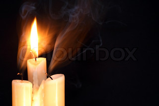 One burning candle between two just extinguished candles on dark background with free space for text