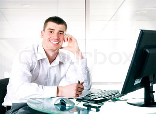 Happy businessman sits at the computer on the office