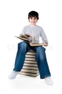 Cute little boy sit on a stack of big books on white background