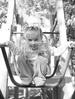 Cute little girl on outdoor playground equipment black-and-white
