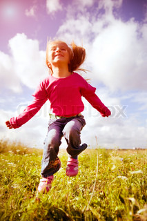 Little girl jumping against a beautiful sky