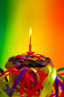 Birthday cupcake with colorful decoration and candle on rainbow background