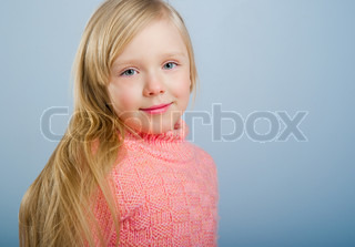 Cute little girl with long hair on a grey background