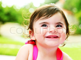 Happy little girl laughing, closeup portrait outdoors