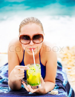 Portrait of a happy young woman drinking cocktail on the beach