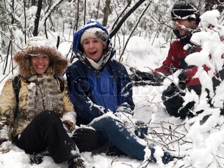 laughing girls sitting in snow forest
