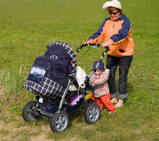 mother with kid carrying the stroller