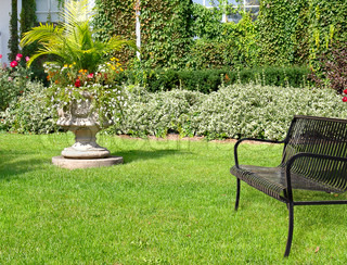 Sunny day in garden with bench and flowers in  sculptural stone planter