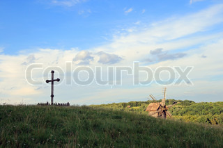 Christian wood cross on grass overgrown hill (forest colony and windmill beyond)