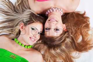 Two beautiful smiling girls with long hair lying down on white