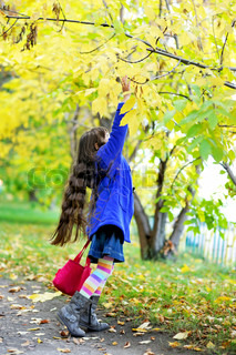 Funky little girl in blue coat standing on tiptoe under the yellow tree