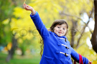 Outdoor portrait of funky little child girl in blue coat holding yellow leaves