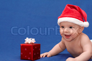 Smiling baby in santa's cap with gift