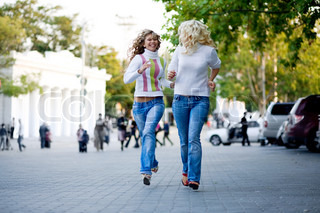 Two teenage girl running in city