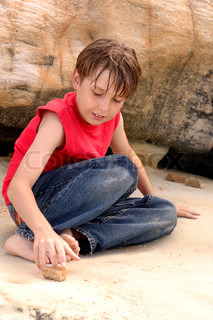 A casually dressed boy amuses himself playing with stones among sandstone rocks outdoors