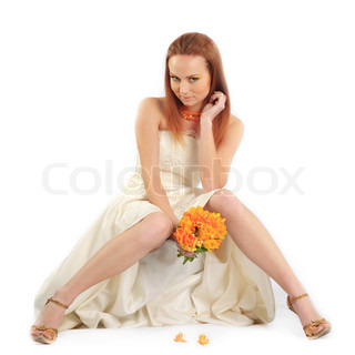 Sexy bride showing her beautiful long legs isolated on white studio background