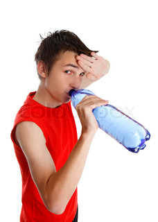 Teen boy wiping his brow and drinking water from a bottle