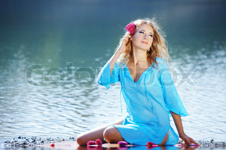 Portrait of young beautiful woman resting near lake