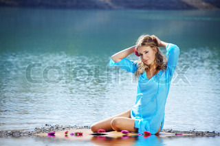 Portrait of young beautiful woman resting near water